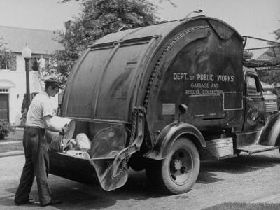 Garbage Man Emptying Trash into Back of Garbage Truck by Alfred Eisenstaedt