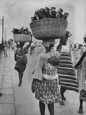 Nigerian Women with Babies Strapped to Their Backs Carrying Large Baskets on Their Heads by Alfred Eisenstaedt