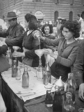 Pouring Olive Oil in Buyers' Bottles in Black Market by Alfred Eisenstaedt