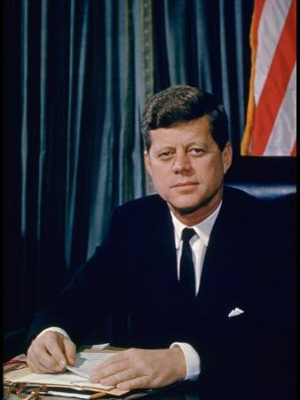 Pres. John F. Kennedy Sitting at His Desk, with Flag in Bkgrd
