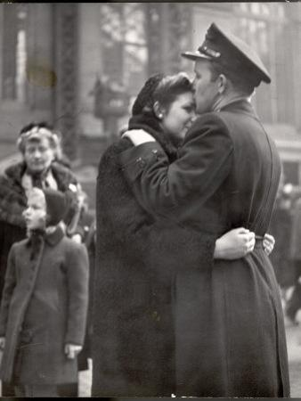 Soldier Tenderly Kissing His Girlfriend's Forehead as She Embraces Him While Saying Goodbye
