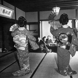 Two Geishas Dancing with Fans on Stage as Guests and Other Geshias Watch from Dinner Table by Alfred Eisenstaedt