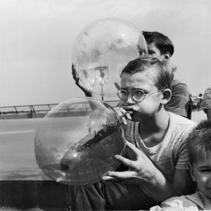 Two Young Boys Blowing Large Transparent Bubbles with a Blow-Straw Dipped in a Soft Plastic by Alfred Eisenstaedt