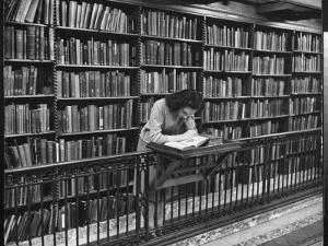 Woman Reading Book Among Shelves on Balcony in American History Room in New York Public Library by Alfred Eisenstaedt
