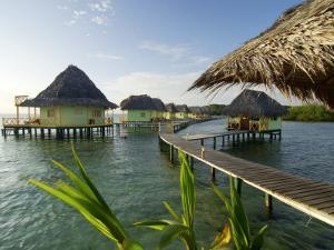 Wooden Walkways Leading Out to Cabins at Punta Caracol Hotel by Alfredo Maiquez
