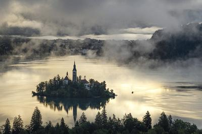 Europe, Slovenia, Bled - A Pletna Boat Arriving At The Island Of Lake Bled During A Foggy Sunrise