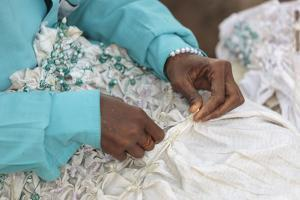 Africa, Gambia, Banjul. Close-up of Woman tying fabric for dyeing. by Alida Latham