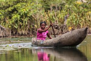 Woman Rowing Traditional Pirogue Down Du River, Monrovia, Liberia by Alida Latham