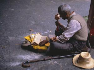 Tibetan Buddhist Pilgrim Reading Texts and Holding Prayer Wheel, Lhasa, China by Alison Wright