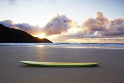 Surfboard Resting on Beach by Allan Baxter