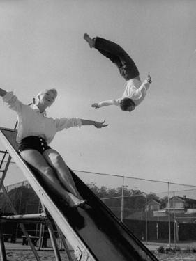 Acrobat and Actor Russ Tamblyn Doing a Flip at a Playground with Movie Actress Venetia Stevenson by Allan Grant