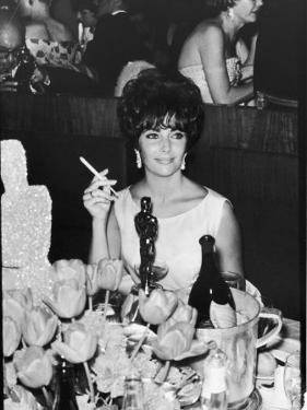 Actress Elizabeth Taylor at Hollywood Party After Winning Oscar, Which is on Table in Front of Her by Allan Grant