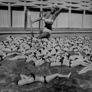 Actress Jayne Mansfield Posing with Shaped Hot Water Bottles Floating around Her at Her Pool by Allan Grant