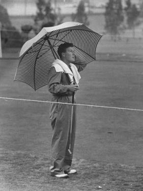 Australian Golfer Peter Thompson, Standing under Oversized Umbrella During the Los Angeles Open by Allan Grant