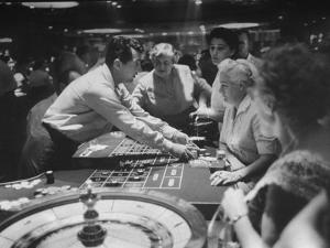Entertainer Dean Martin Acting as Dealer at a Casino by Allan Grant