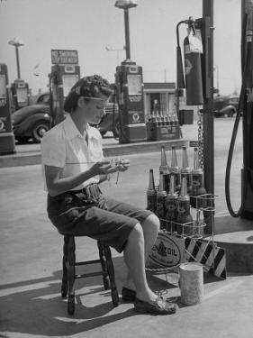 Girl Change Maker Knitting During Slow Moments at the Gilmore Self-Service Gas Station by Allan Grant