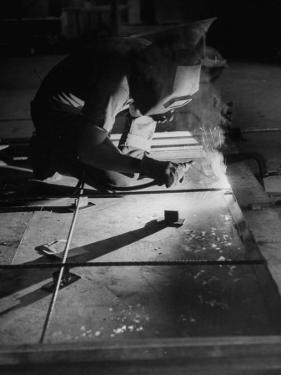 Man Welding Pieces of Metal Together by Allan Grant
