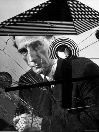 Marcel Duchamp Sitting Behind Example of Dada Art