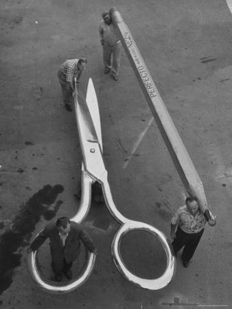 Stagehands Pushing a Pair of Gigantic Scissors on a Dollie Next to Two Men Carrying a 21 Ft. Pencil