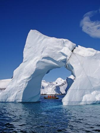 Grandidier Channel, Tourists Zodiac Cruising by Arched Iceberg Near Booth Island, Antarctica