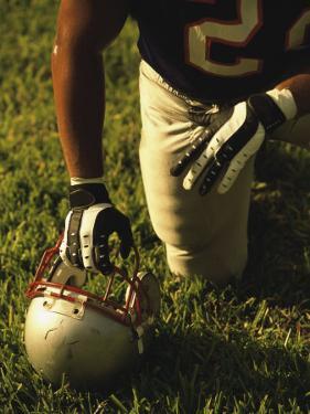 American Football Player Kneeling on the Field