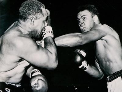 Young Cassius Clay Scores with a Left Against the Veteran Archie Moore in the First Round of the… by American Photographer