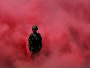 Amidst Smoke from a Flare, a Soldier Attends a Military Ceremony in Cali, Colombia
