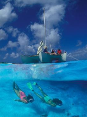 Female Divers Submerged Below Catamaran by Amos Nachoum