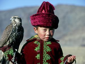 Young Boy Holding a Falcon, Golden Eagle Festival, Mongolia by Amos Nachoum