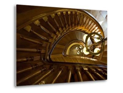 Looking Down a Spiral Staircase Past a Hanging Chandelier by Amy & Al White & Petteway