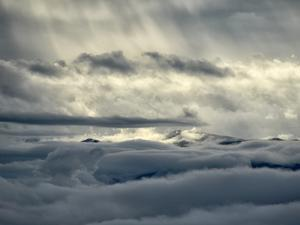 Sunlight Shines Through Clouds on a Sea of Clouds Below by Amy & Al White & Petteway