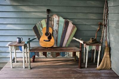 A 1931 Martin 0-28 Guitar Rests on a Re-Purposed Furniture Bench on a Front Porch