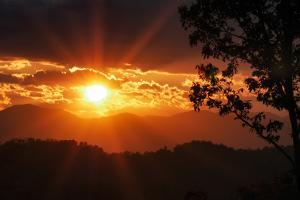 The Sun Sends Out Rays of Light as it Sets over the Mountains by Amy White and Al Petteway