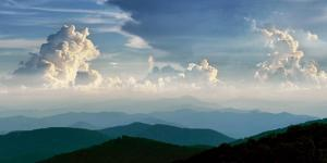 Cumulonimbus thunderhead clouds form over the Blue Ridge Mountains on a summer day. by Amy White