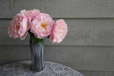 Pink rose blossoms are set in a blue vase. by Amy White
