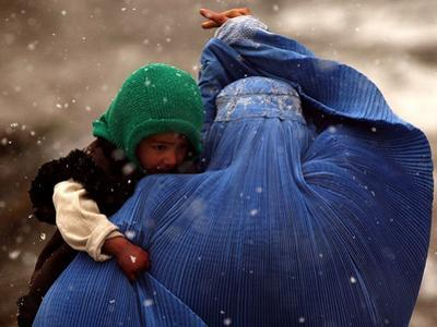 An Afghan Woman Holding Her Child Throws Back Her Burqa to See Her Way Along a Muddy Alley