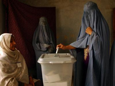 An Afghan Woman Wearing a Burqa Casts Her Ballot at a Polling Station
