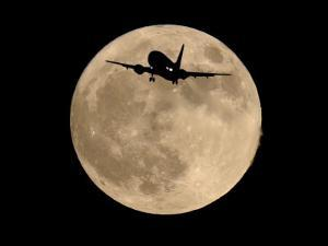 An Airliner is Silhouetted against a Full Moon