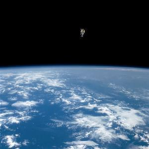 An astronaut propelled above the earth with a nitrogen jet backpack