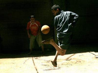 An Egyptian Boy Shows off His Ball Skill as He Plays Soccer with a Friend on the Steets of Cairo