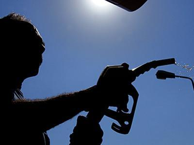An Employee of a Petrol Station Holds a Petrol Pump after Filling up a Car