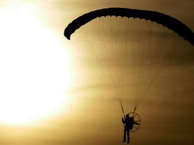 An Engine-Powered Paraglider Soars Through the Air Near Schlesen