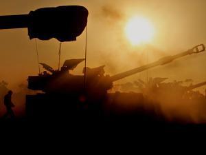 An Israeli Soldier Runs to Reload an Israeli Mobile Artillery Piece