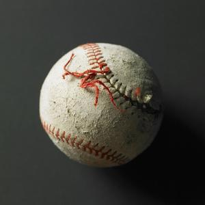 An old baseball with its stich ripped