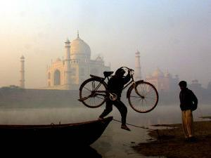 An Unidentified Cyclist Gets Down with His Cycle against the Backdrop of the Taj Mahal