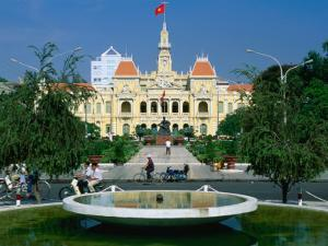 People Riding Bikes Past Fountain and Town Hall, Ho Chi Minh City, Ho Chi Minh, Vietnam by Anders Blomqvist