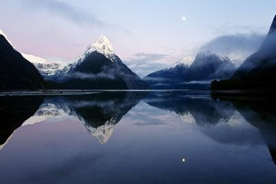 New Zealand, Nuova Zelanda, Fiordland, Milford Sound and Moon During a Cold and Misty Sunrise.