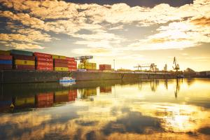 One of Main River's side channels with stacked containers and golden reflections in an industrial s by Andreas Brandl