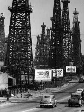 Car Traffic on Highway Next to Advertising Billboards and Oil Well Towers, Signal Hill Oil Field by Andreas Feininger
