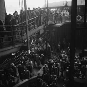Ferry Boat Commuters from Staten Island Disembarking at Ferry Slip in Manhattan by Andreas Feininger